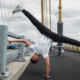 A guy doing a hand stand on bridge